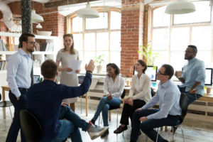 Ambitious male employee raise hand ask question to female presenter at meeting, man show activity at teambuilding with multiethnic colleagues, diverse workers brainstorm at office education briefing